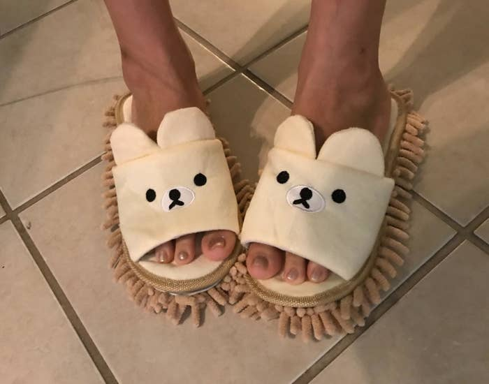 reviewer wears bear slippers with mop soles