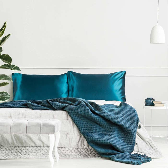 Two teal satin pillowcases on a bed