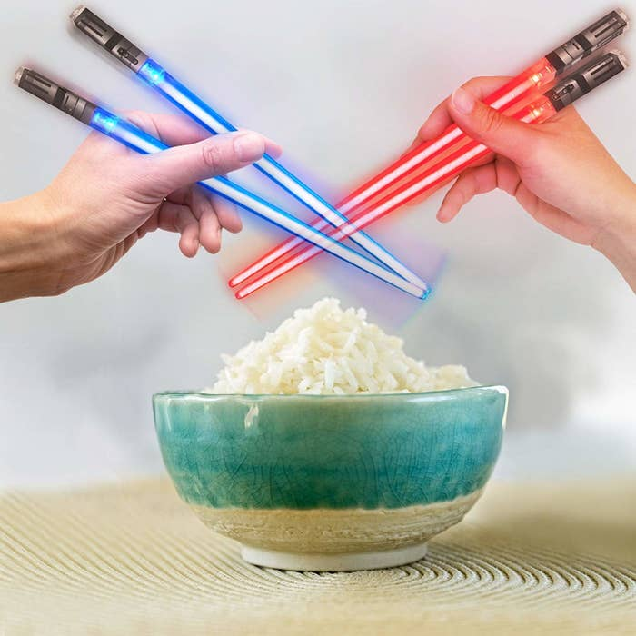 Two people holding the chopsticks over rice