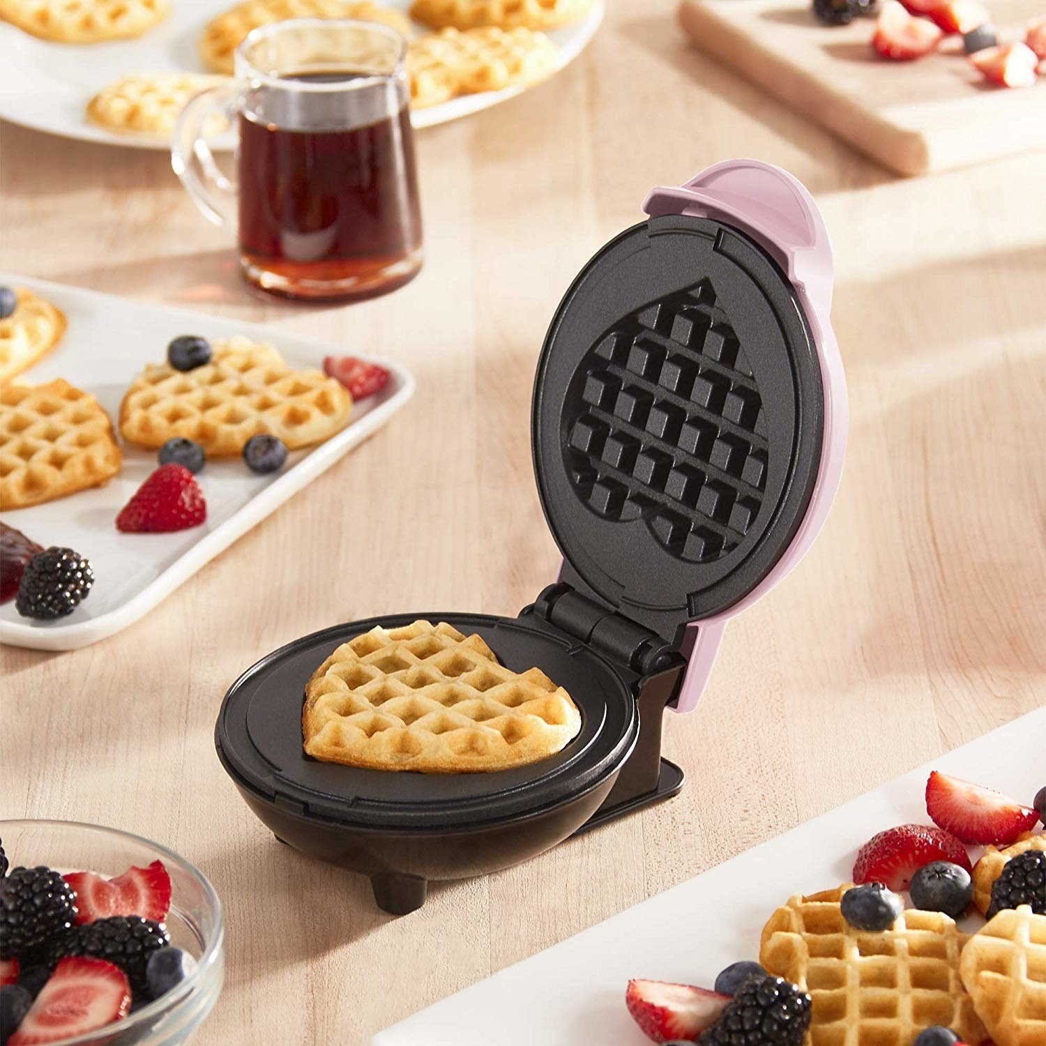An open mini waffle maker with a fully cooked heart-shaped waffle inside