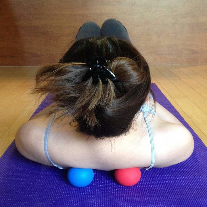 A model rolling on a yoga mat with the two balls on either side of their spine
