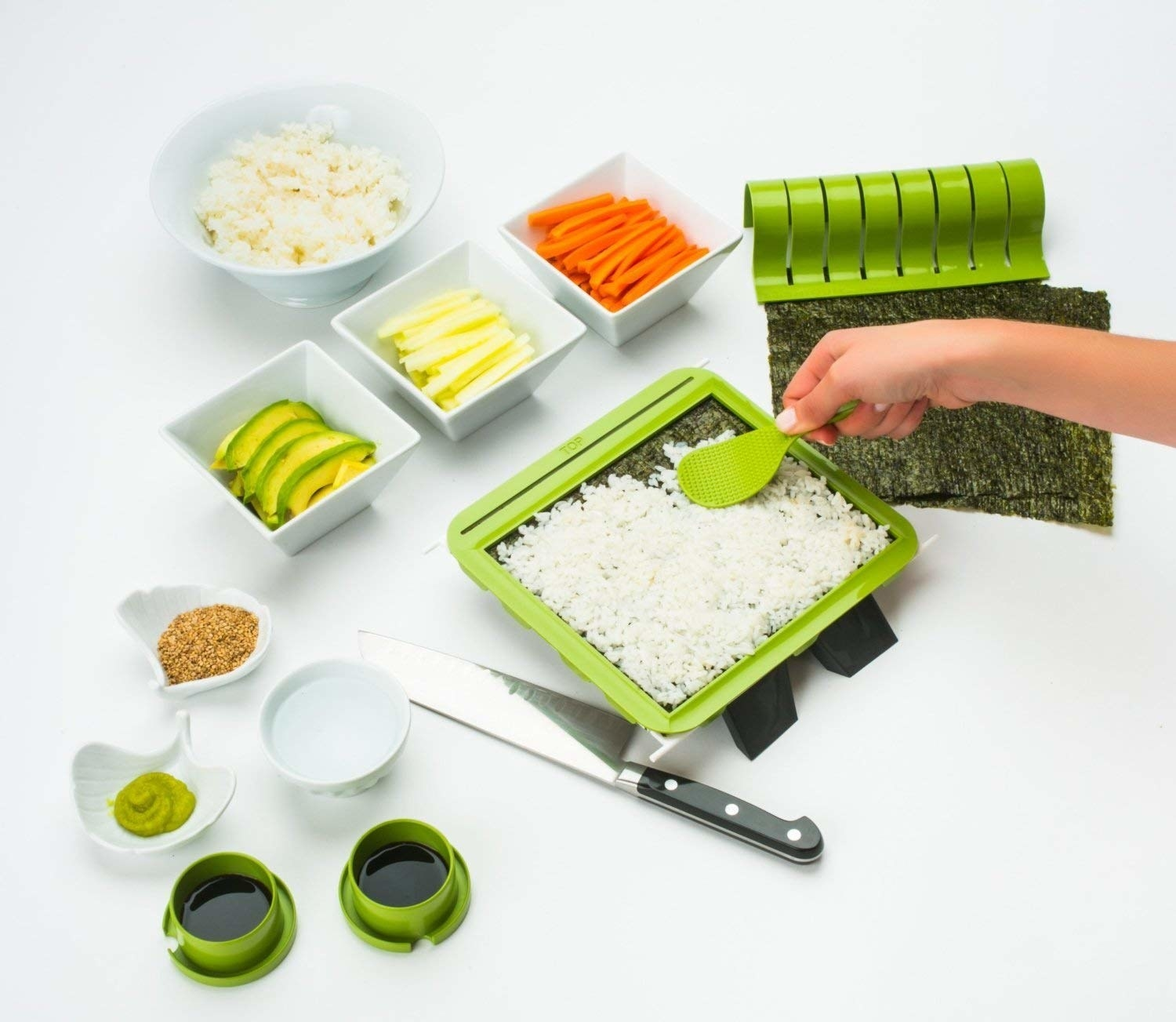 A person making sushi with the kit, including a tray and a roller for the rice