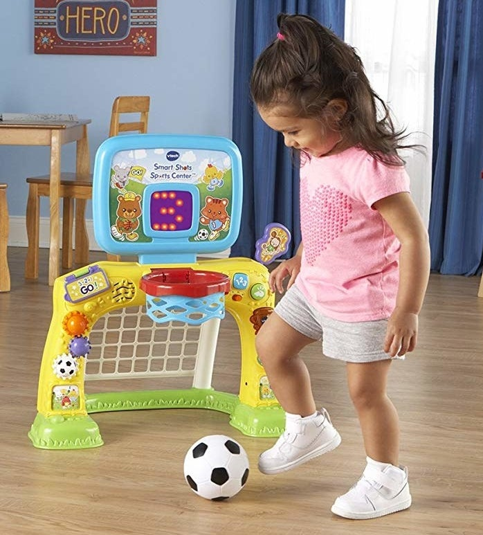A child model playing with a small soccer ball near the colorful plastic sports center
