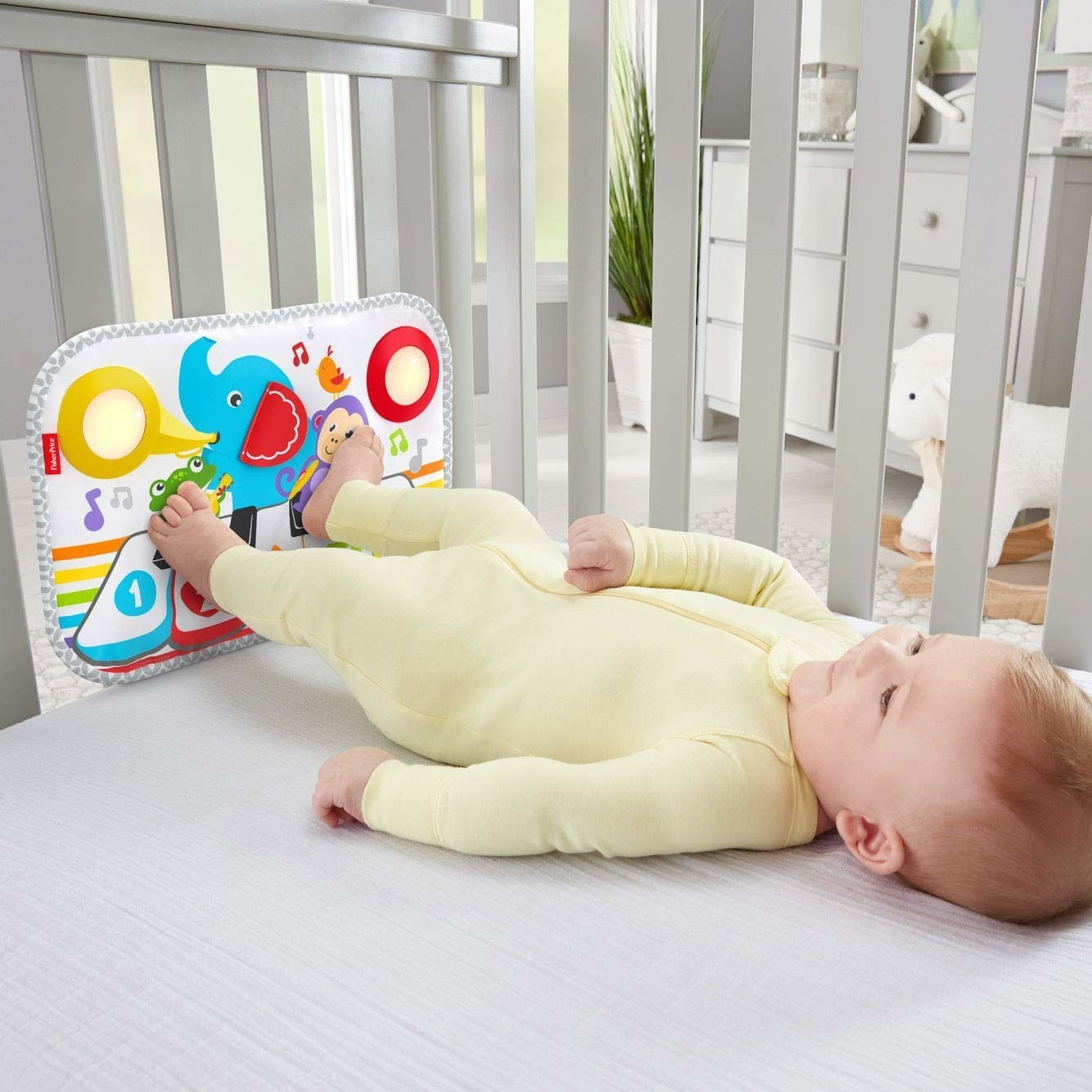 A child model in a crib playing the colorful piano with their feet