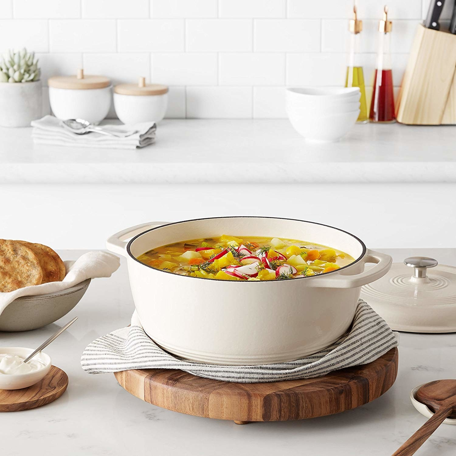 the Dutch oven in white filled with soup