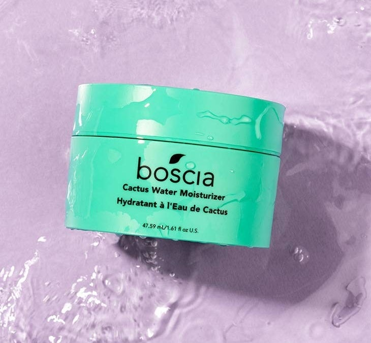 A close up of the moisturizer against a watery background