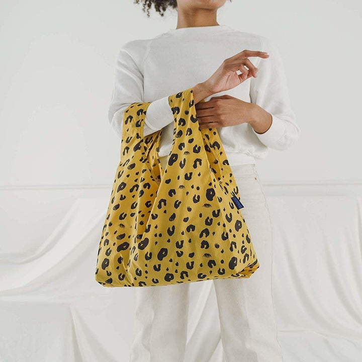 a model holding the leopard-print bag