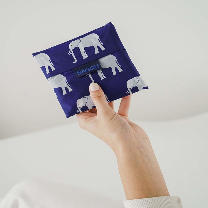 a hand holding a blue bag with elephants on it that's folded into a small square