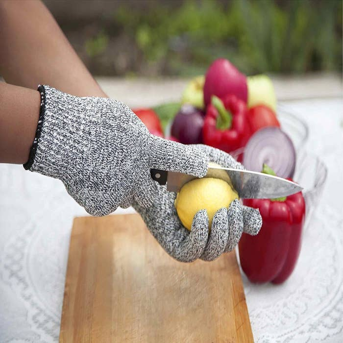 A hand cutting a fruit while wearing the gloves.
