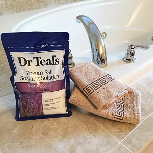 a re-sealable bag of lavender epsom salt next to a bath tub