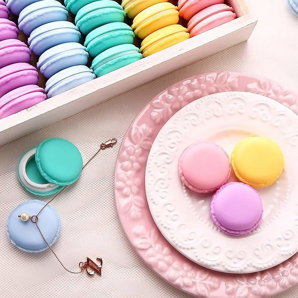 A plate with three macaron shaped container on it