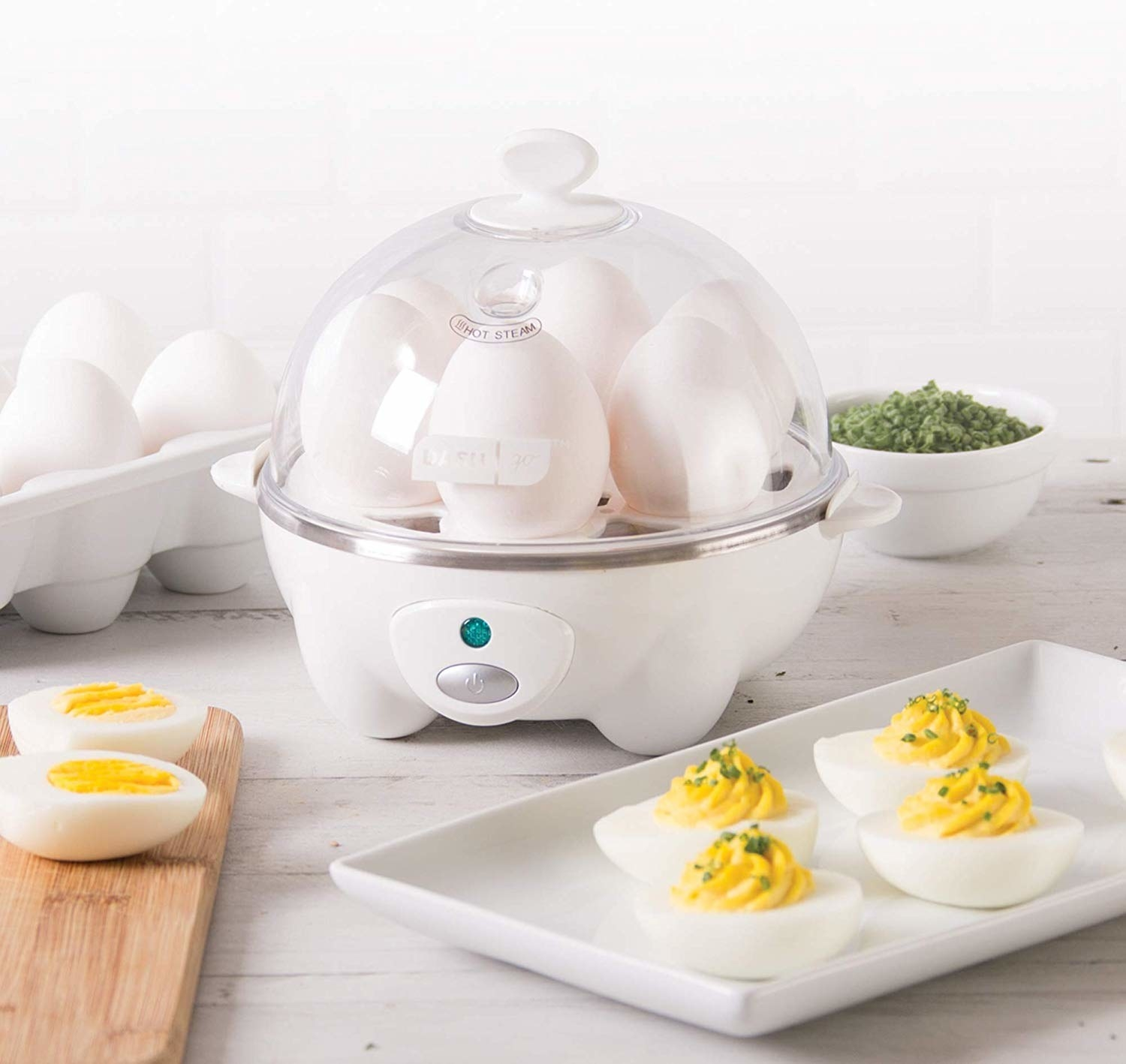 An egg cooker with a transparent dome plastic top, where six eggs are cooking inside