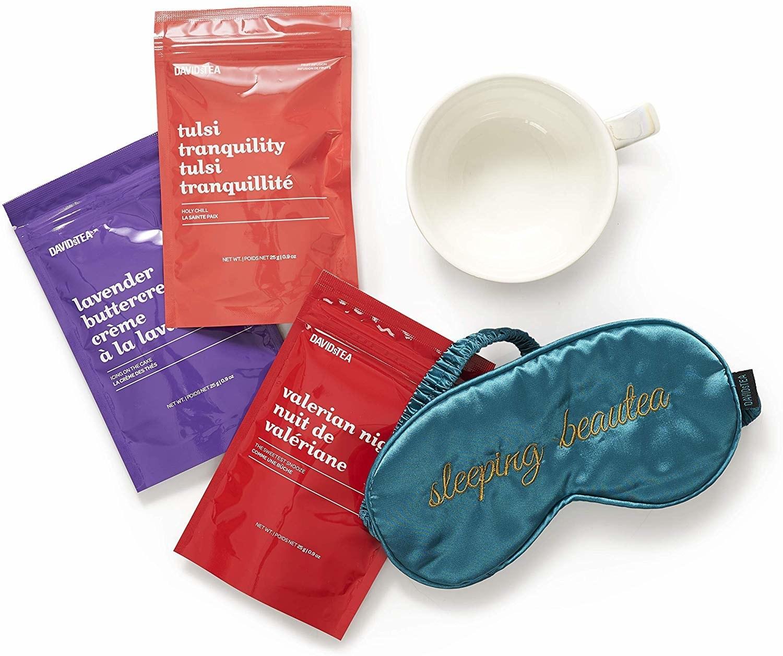 A flatlay of the three included teas, a mug, and a sleeping mask