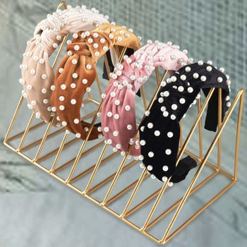 four different colored velvet headbands with pearls