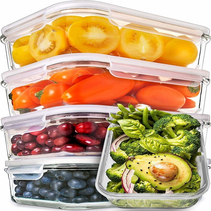 five transparent glass stacked tupperwares with clear lids and food in them