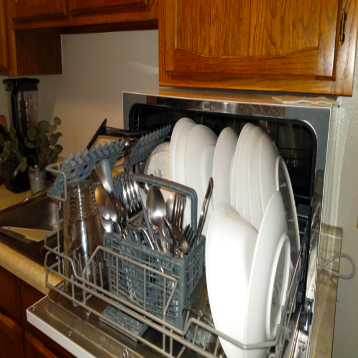 The dishwasher open, holding several plates and utensils