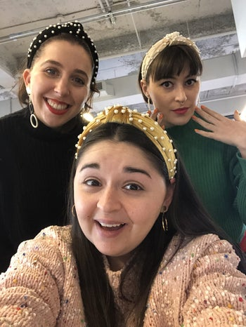three buzzfeed employees wearing velvet headbands with pearls on them