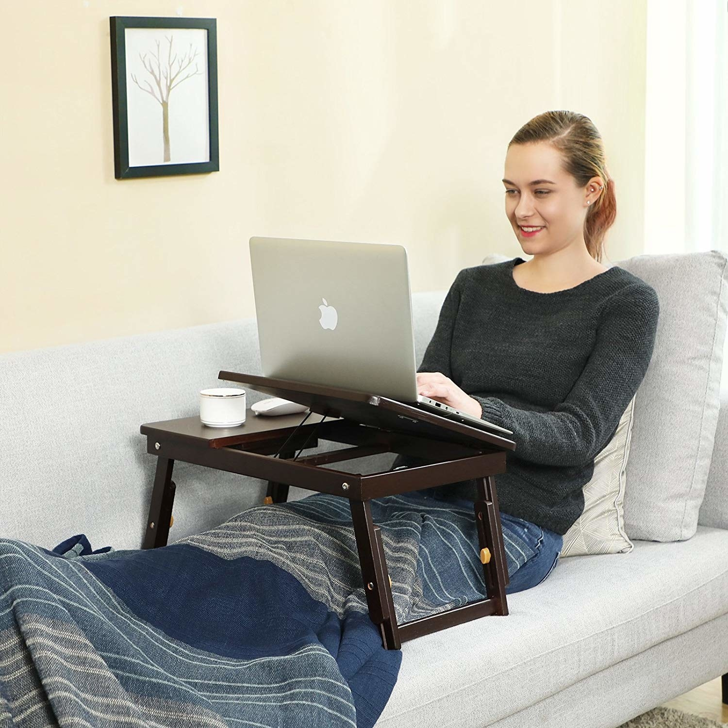 model with the brown wood desk over their lap on a couch with one half raised up, bringing a laptop higher