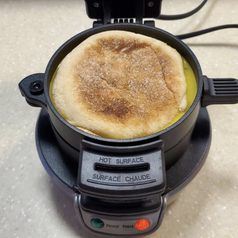 A reviewer image of an English muffin sandwich cooking in the machine