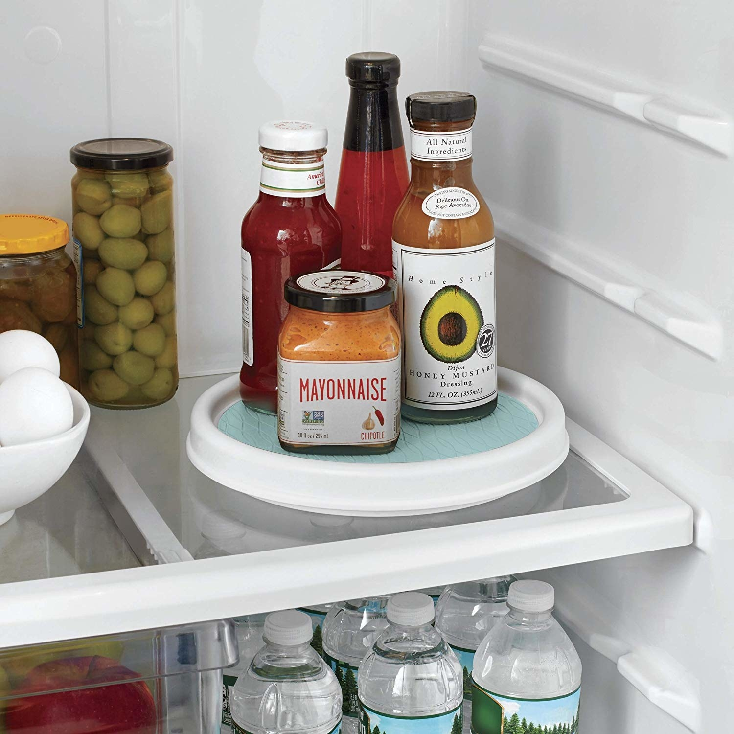 A small white turn table in a fridge with condiments on top of it