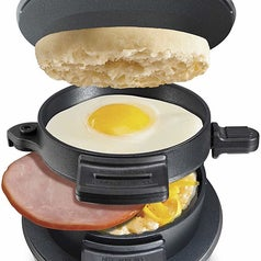 A product image of the machine cooking an egg, English muffin slices, cheese, and a piece of ham