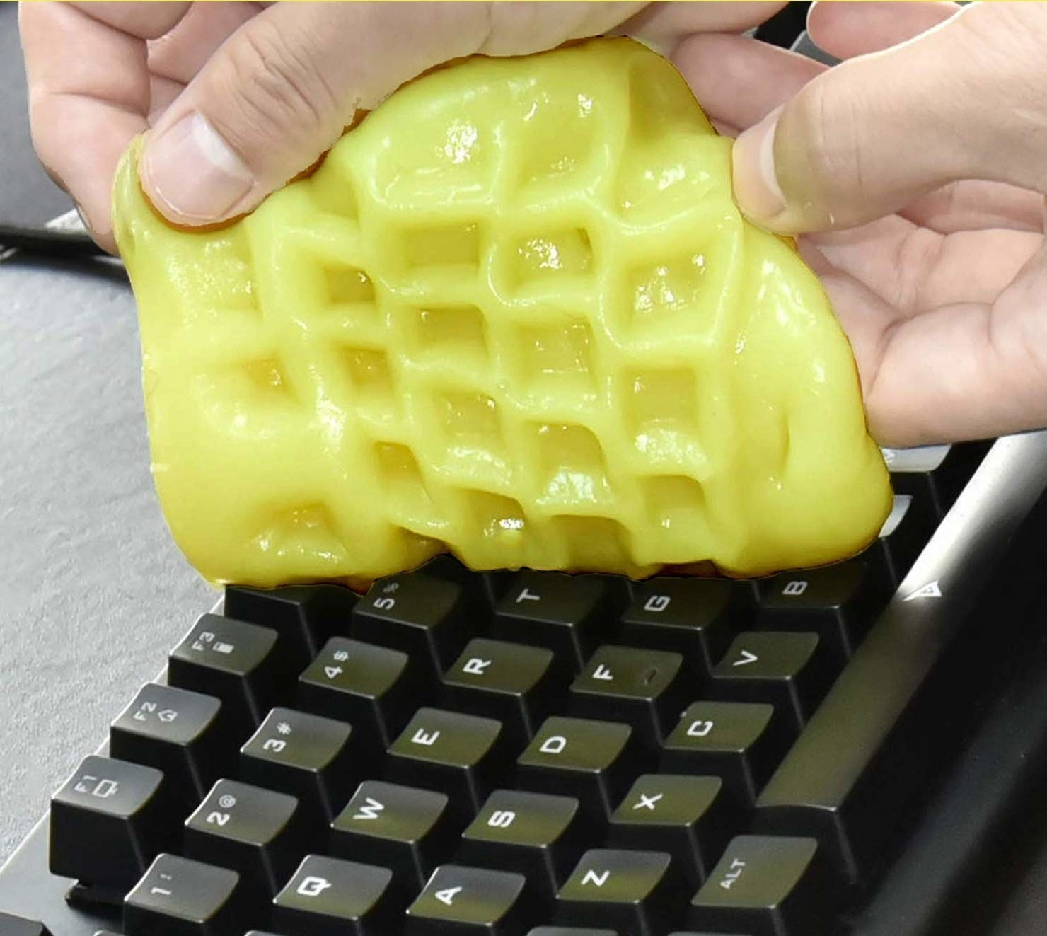 A close up of a person using the goo on a keyboard