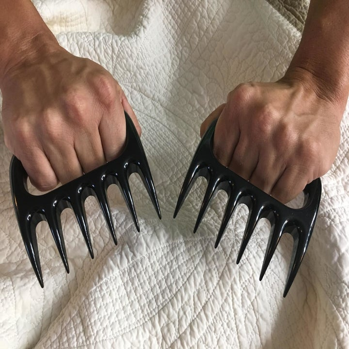 Reviewer with their fingers wrapped around the handles of two claw-like plastic shredders