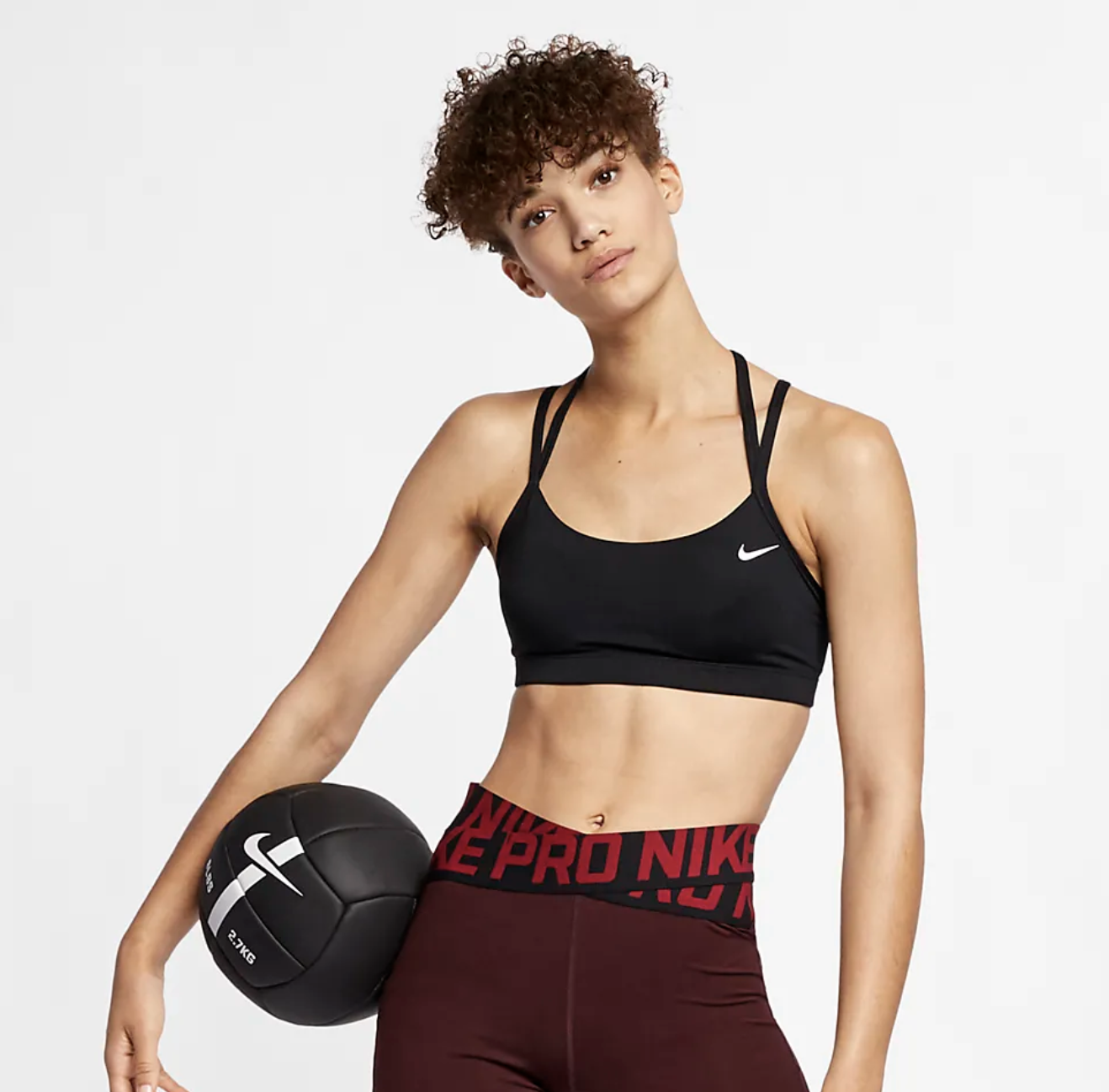 Model wears black Nike Women's Light-Support Sports Bra with dark red shorts