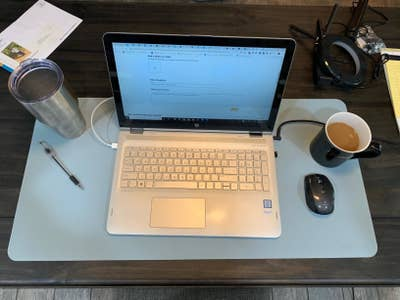 Reviewer pic of the rectangle desk mat in blue with laptop, coffee, mouse and pen on it