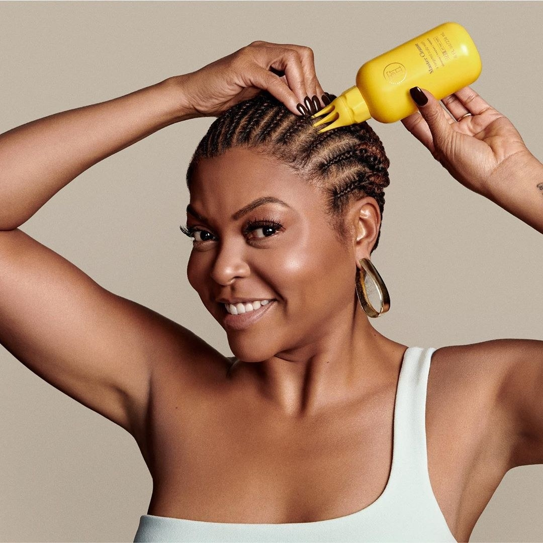 Actress Taraji P. Henson pouring the bottle of scalp conditioner directly to her scalp