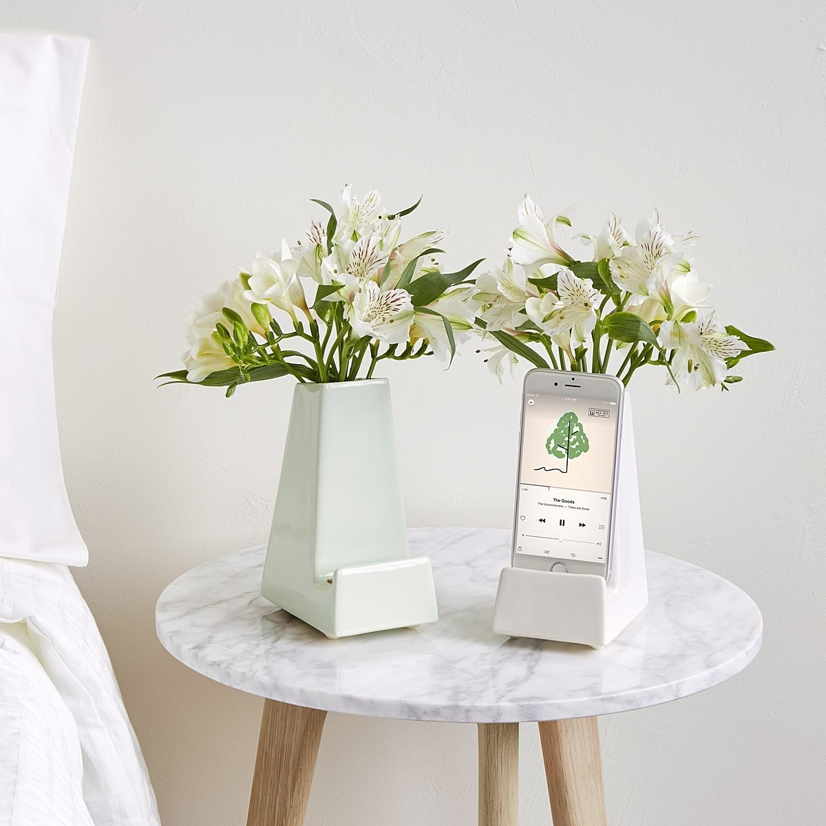 Two phone stands, one mint and one white, with flowers coming out of a small vase at the back