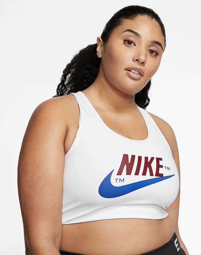 Model wears white Nike Swoosh Icon Clash sports bra