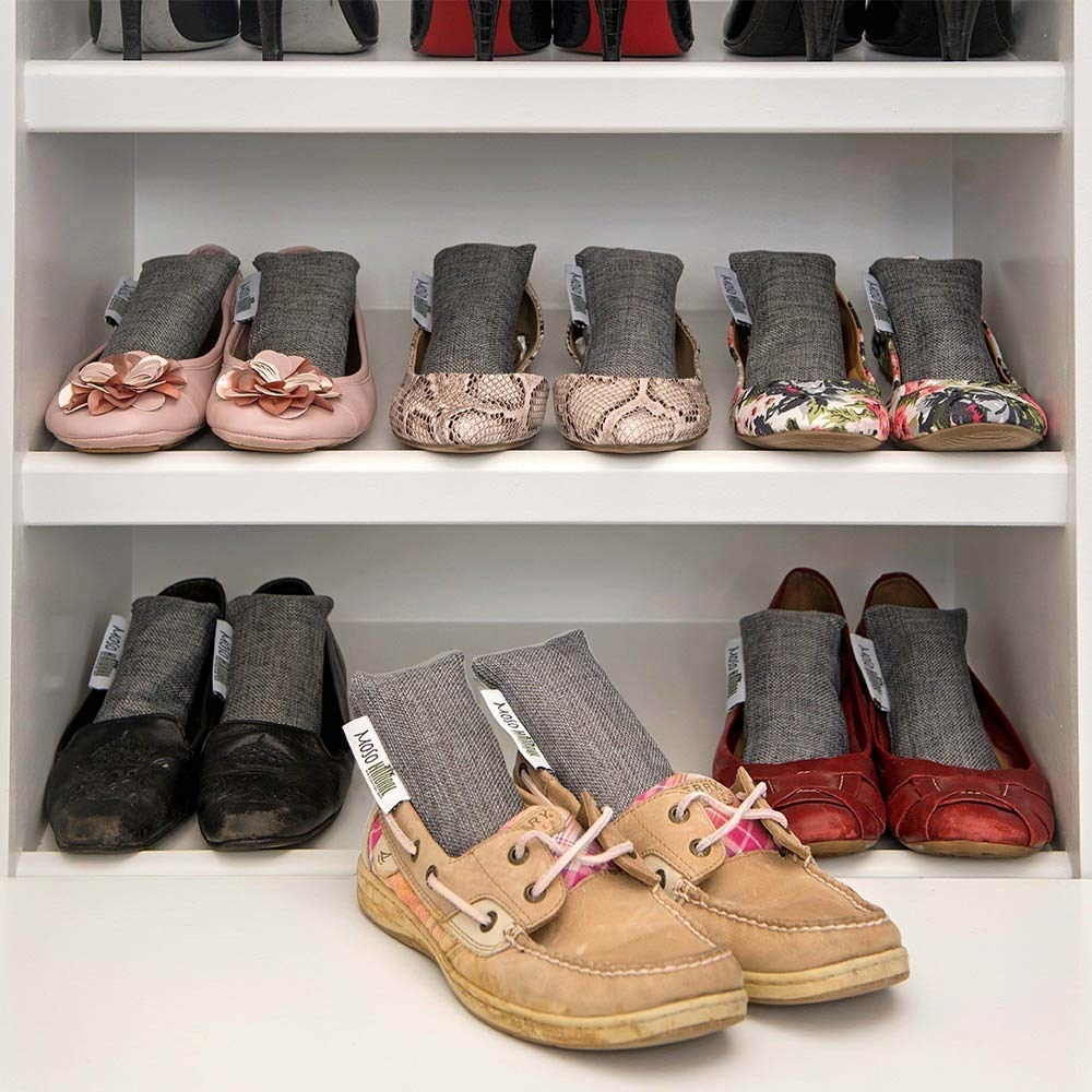Six pairs of shoes on a shoe rack with small dedodorizing sachets sitting in each one