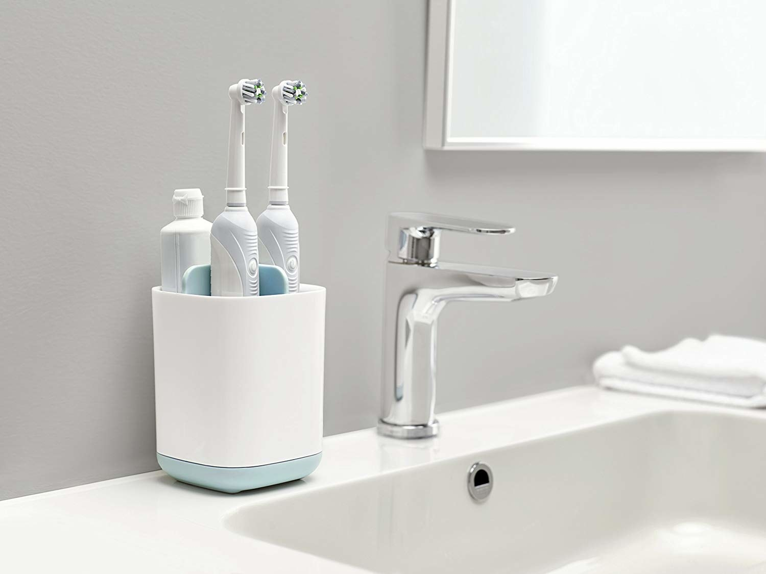 A square-shaped toothbrush holder with four slots sitting on a bathroom counter Two slots have electric toothbrushes in them and one has a tube of toothpaste