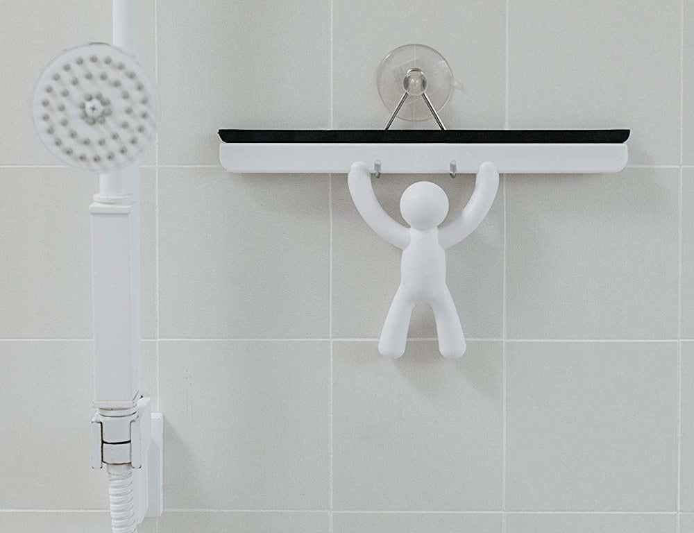 A shower squeegee hanging from a suction cup hook on a bathroom wall The handle is shaped like a person