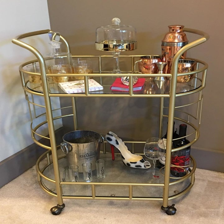 reviewer's gold cart with bottles of alcohol, glasses, and other drink-making accessories on it