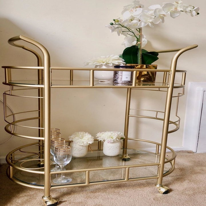 reviewer's gold cart with vases and flowers on it