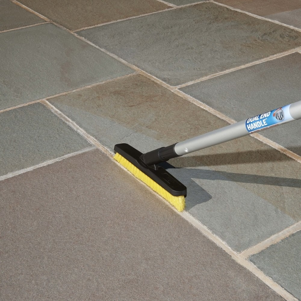 Model using grout brush attached to broom handle to clean in between tiles