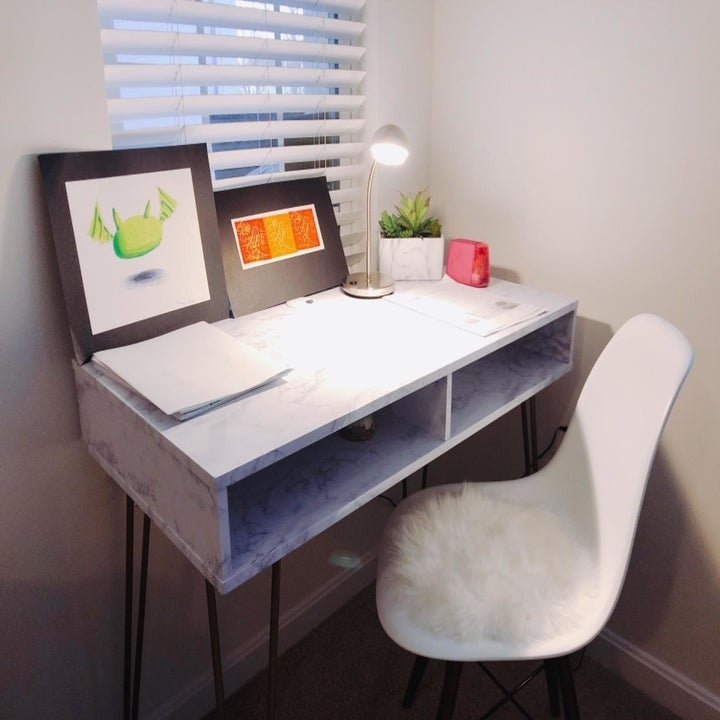 reviewer's desk with a desk lamp and decorations on it