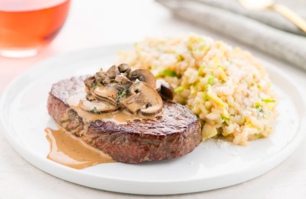 A prepared meal with steak, mushrooms, gravy, and risotto