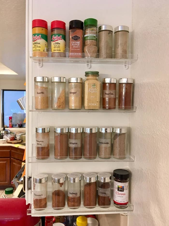 four narrow clear acrylic shelves on side of reviewer's kitchen cabinets, each with about six jars of spices each