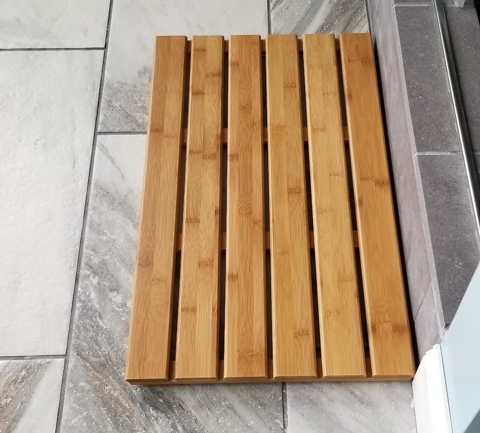 a reviewer photo of the slatted bamboo mat on the floor of their bathroom