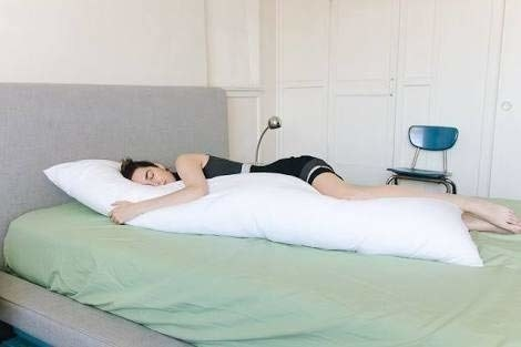 Woman sleeping with a body pillow.
