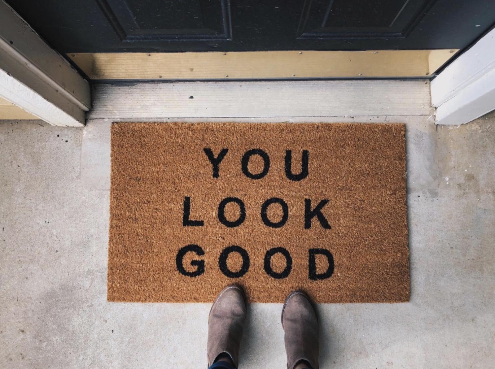 """Reviewer standing above the """"You Look Good"""" doormat"""