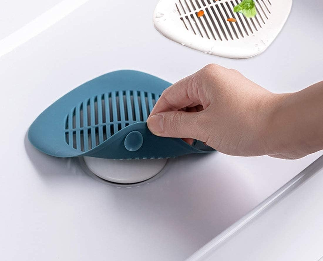 Hand lifting the silicone drain cover to show it protecting a sink drain