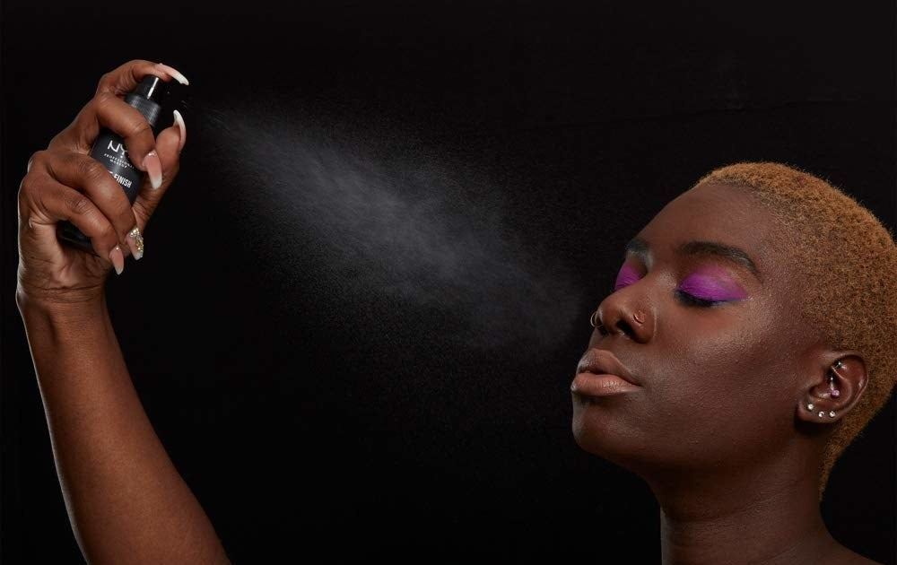 A person sprays setting spray onto their face.