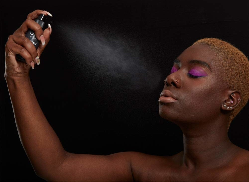 A person sprays products onto their face