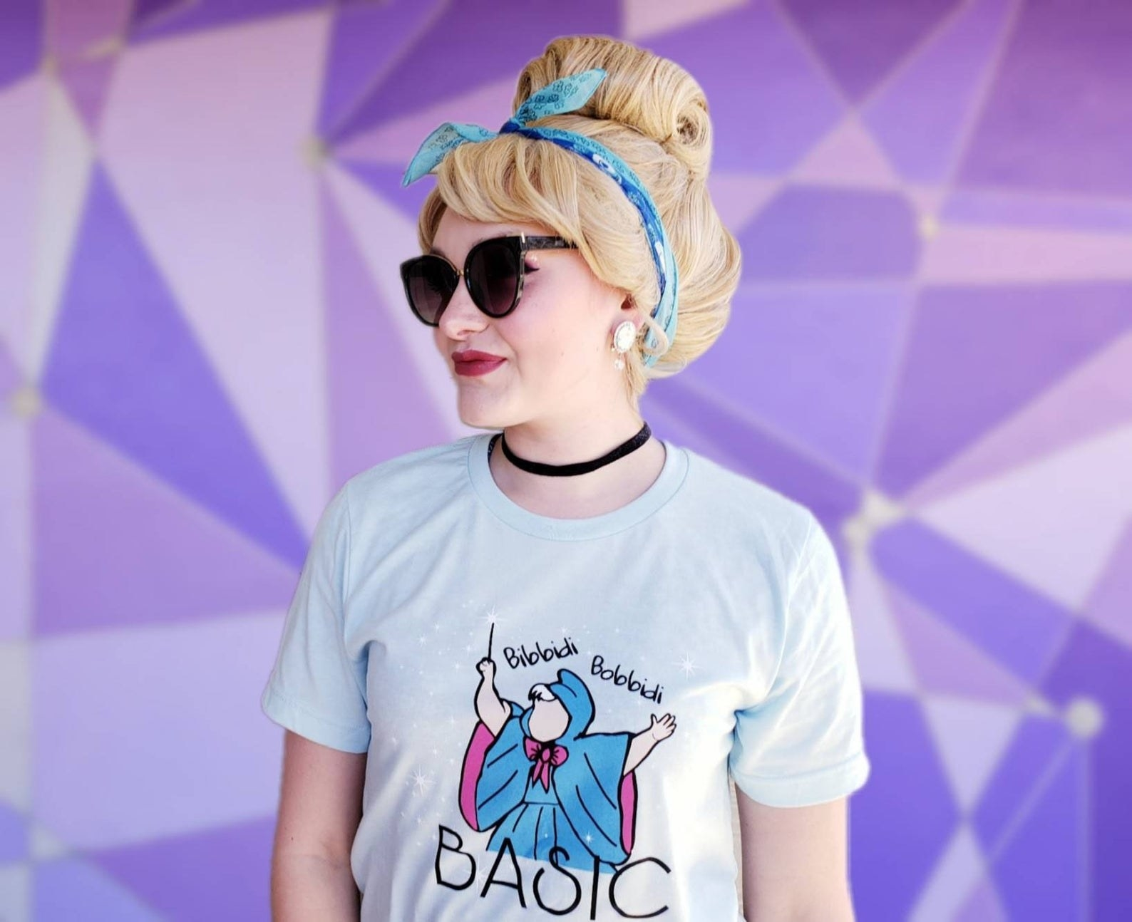 "a model in a light blue tee with an illustration of fairy godmother on it and ""bibbidi bobbidi basic"" written on it"