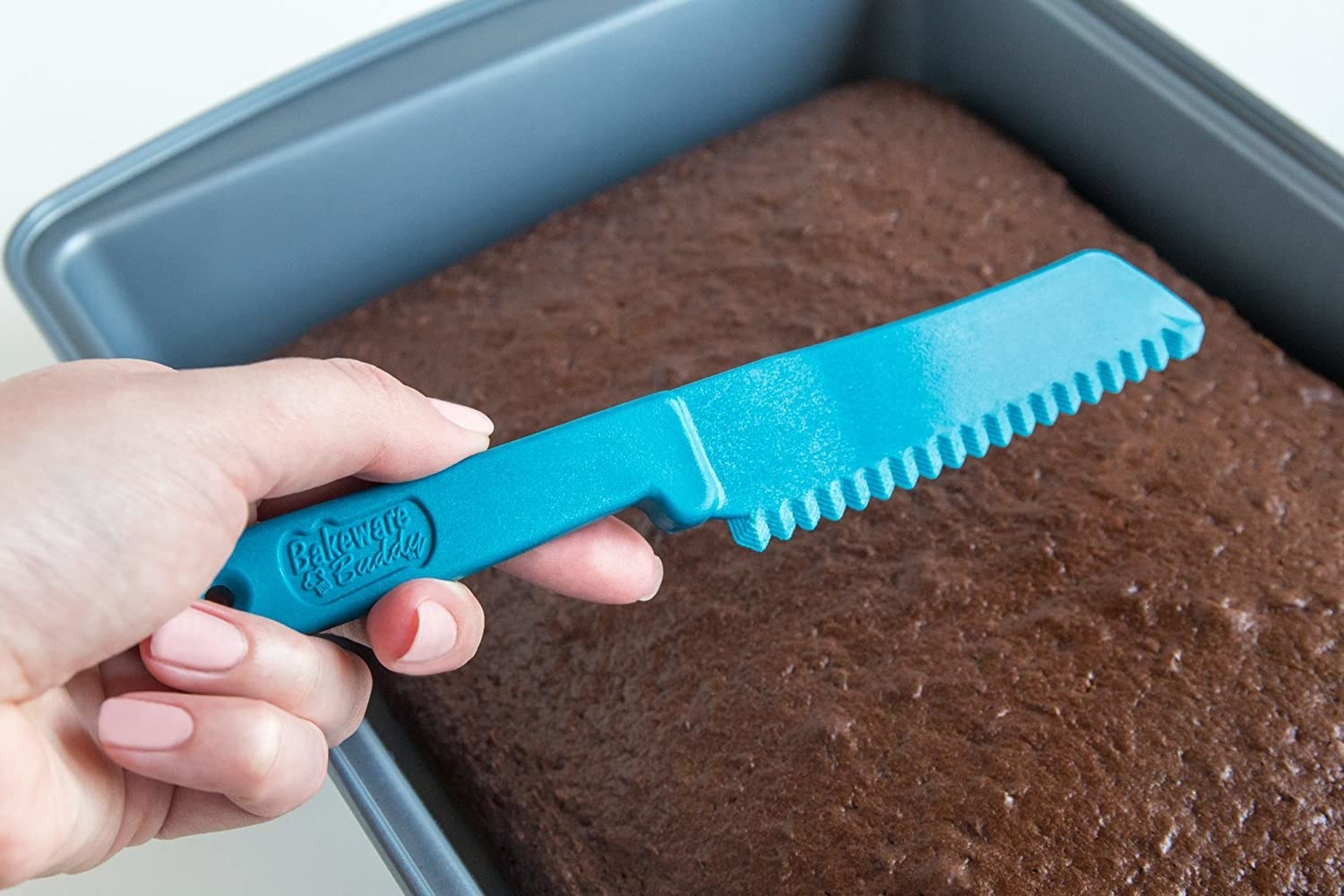 A person holding the baking knife over a sheet cake