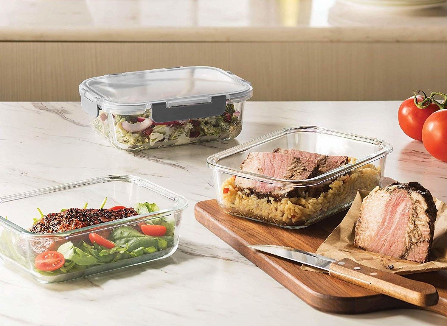 a salad, meat and rice, and salmon inside meal prep containers